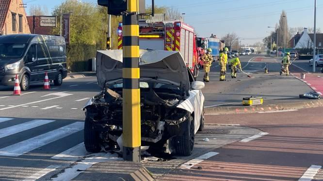 Automobiliste knalt met BMW tegen verkeerslichten en -borden op kruispunt