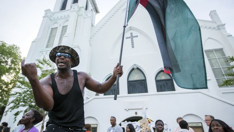 Amerikaanse man protesteert tegen racisme nabij de kerk van Charleston waar vorige week een blanke jongeman negen zwarte mensen neerschoot. Beeld AP