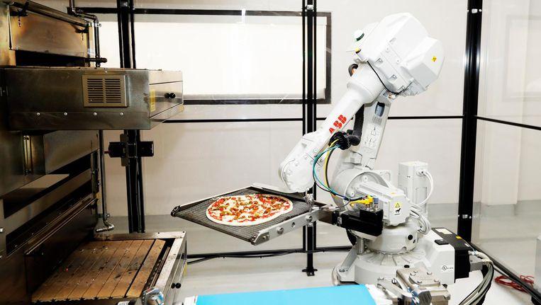 Een robot in Californië bakt een pizza. Beeld null