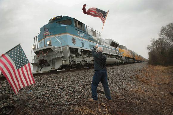 Peter Olyniec zwaait met een Amerikaanse vlag wanneer de trein met het lichaam van de overleden president Bush voorbij komt gereden in Whitehall, Texas.