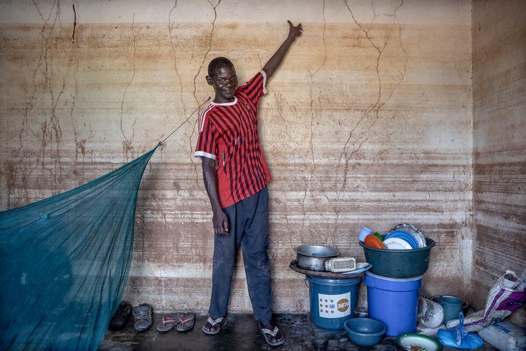 Carlitos João woont in Buzi, op 25 kilometer van Beira. Hij verloor zijn vrouw bij de ramp van maart. Hij wijst hier naar de bovenste modderstreep die het water achterliet op de muren van zijn huisje. Beeld Sven Torfinn