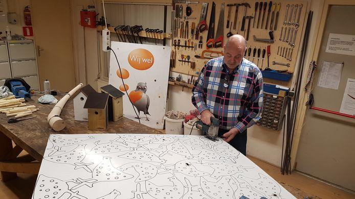 'Veurman' Hermy Oude Veldhuis zaagt de kippen uit een van de aluminium platen die dienst hebben gedaan als reclamebord langs het voetbalveld.