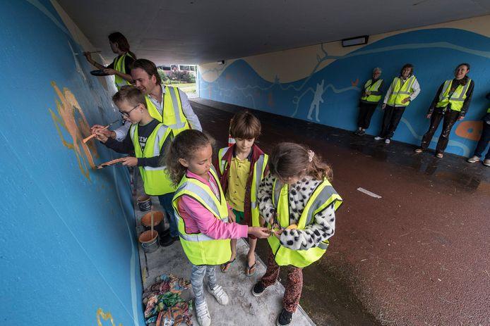 Kinderen leggen de laatste hand aan het schilderwerk in de Berenkuil, wethouder Frank Groen helpt een handje mee.