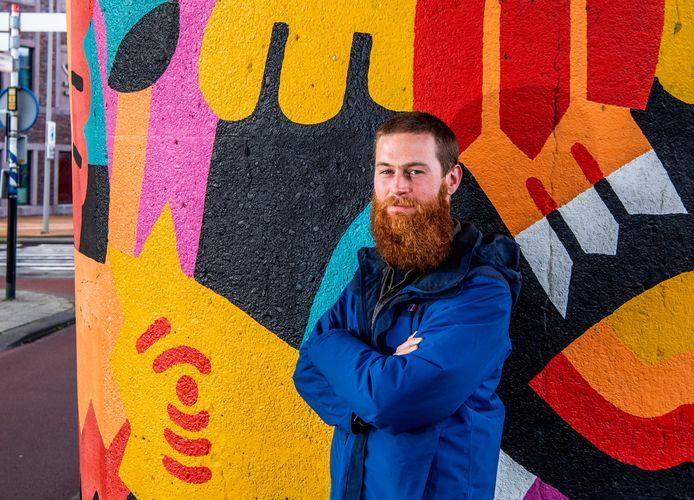 Illustrator Thijs Lansbergen bij zijn muurschildering op een metropaal bij de Maashaven.