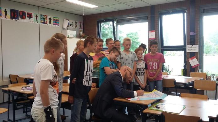 Wethouder Han Looijen ondertekent samen met de leerlingen van groep 8 van de School met de Bijbel in Zuilichem een 'safetydeal' over veilig gebruik van de mobiele telefoon op de fiets.