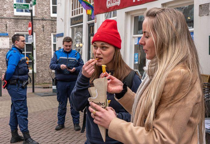 Genieten van snacks, terwijl boa's ingrijpen bij de verkoop van alcohol tijdens de eerste Frituurloop in Zwolle.