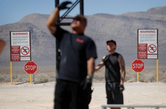 Medewerkers van een evenement bouwen een podium vlak voor waarschuwingsborden voor de militaire basis.