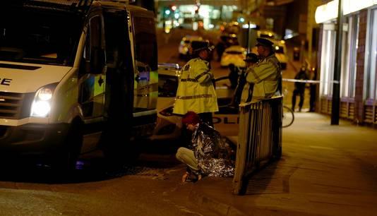 Een vrouw wordt buiten de concertzaal warm gehouden naast een politiebusje.