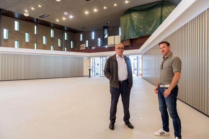 Bestuurslid Theo van den Hoven (l) en projectleider Ronald Witte in het middenschip, dat is verkleind door twee schuine wanden in de ruimte. Volgende maand worden de kerkbanken teruggeplaatst.