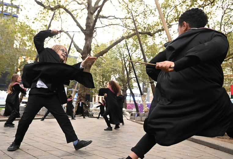 Een tovenaarsgevecht op klaarlichte dag. Leerlingen van een school in Londen leren van de choreograaf van de Harry Potterfilms hoe je moet vechten met een toverstok. Het is twintig jaar geleden dat de film Harry Potter en de Steen der Wijzen werd uitgebracht.  Beeld REUTERS