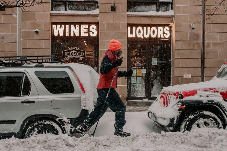 Een wandelaar houdt zich staande met skistokken in de besneeuwde straten van Brooklyn.  Beeld Getty Images
