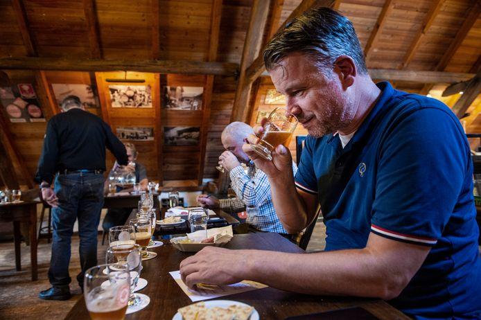 Juryvoorzitter Rob Scheepers keurt een van de 54 inzendingen voor Brabants Lekkerste Bier. Naast hem ontfermt ook Ton van Opstal zich over zijn taak, terwijl Albert Bull zich nog laat inschenken.
