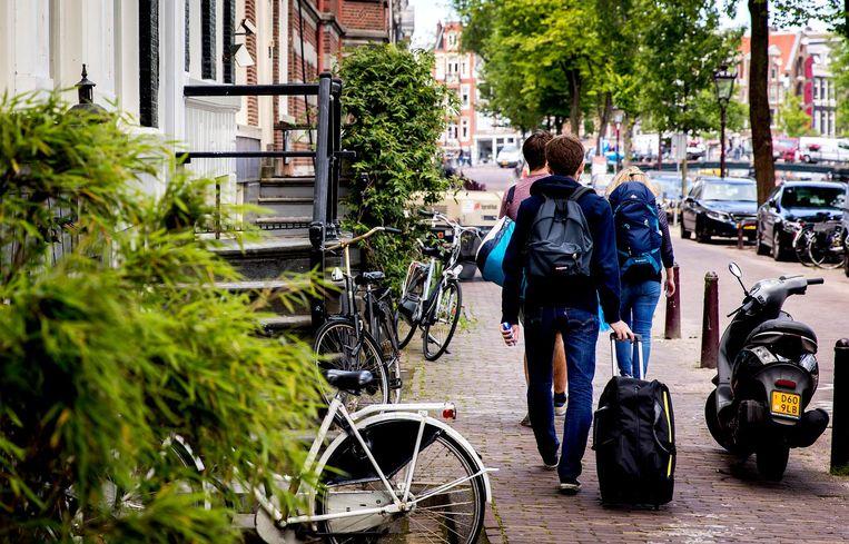 Toeristen lopen met hun koffers over de Amsterdamse grachten. Beeld ANP