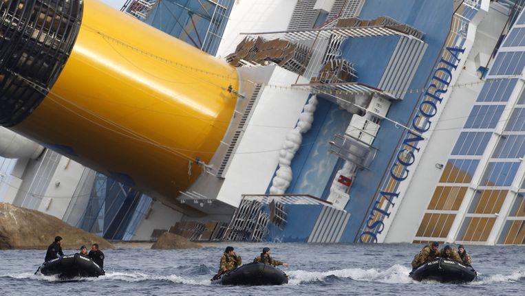 Duikers van het Italiaanse leger keren terug nadat ze in het gekapseisde schip naar overlevenden hebben gezocht. Beeld ap