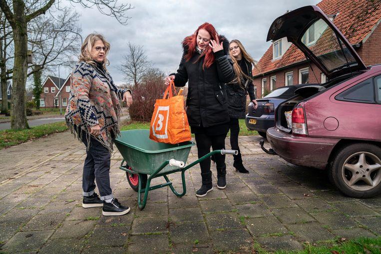 Hilda Knegt (links) van dierenvoedselbank de Gouden Poot in Vlagtwedde helpt twee klanten met hun spullen. Beeld Reyer Boxem