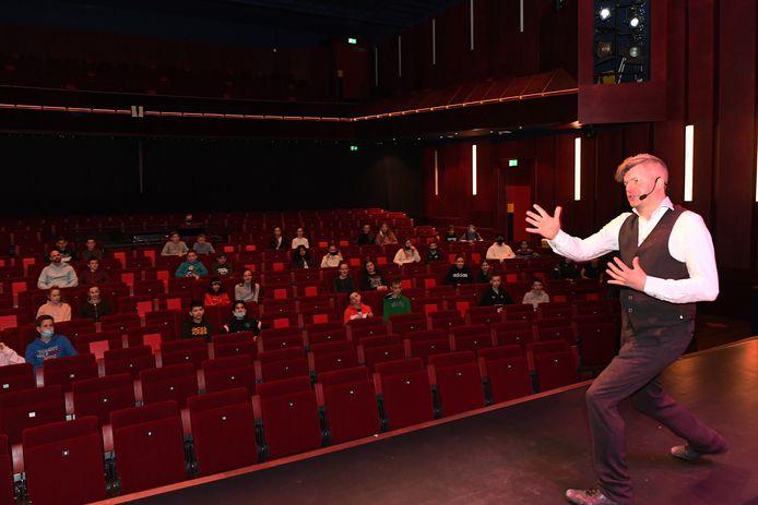 Jo de Rijck speelt zijn voorstelling 'Maak je dromen waar' voor leerlingen van het Merletcollege. Die zitten in duo's op veilige afstand van elkaar.