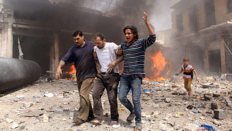 Syrische mannen helpen een gewonde man na een bombardement op Aleppo. Activisten stellen dat het bombardement werd uitgevoerd door het Syrische regeringsleger. Beeld null