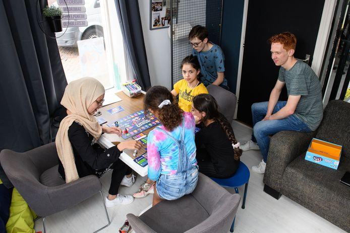 Ilhaam Ouamari (links) doet een bordspel met Eliza, Mareym en Malak, terwijl Harmen Mulder (met bril) en  Jelle Oonk toekijken.