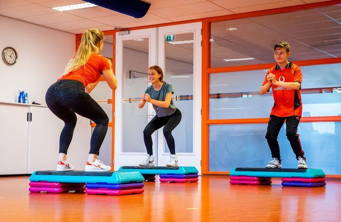 Fysiotherapeut Melissa Oosting doet oefeningen voor aan Josefien (links) en Ian (rechts).