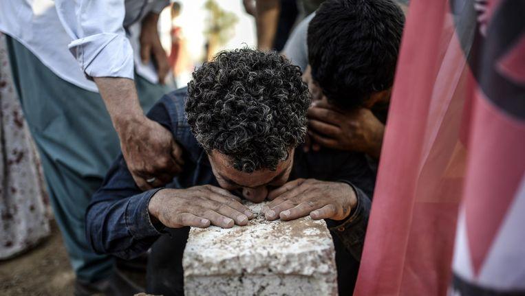 Een man rouwt dinsdag tijdens de begrafenis van slachtoffers van de bomaanslag in het Turkse Suruç, waarbij 32 doden vielen Beeld afp