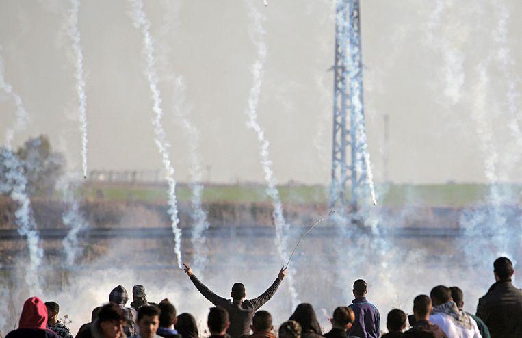 Palestijnse demonstranten omgeven door traangas dat het Israëlische leger gisteren inzette in de bezette gebieden.  Beeld EPA