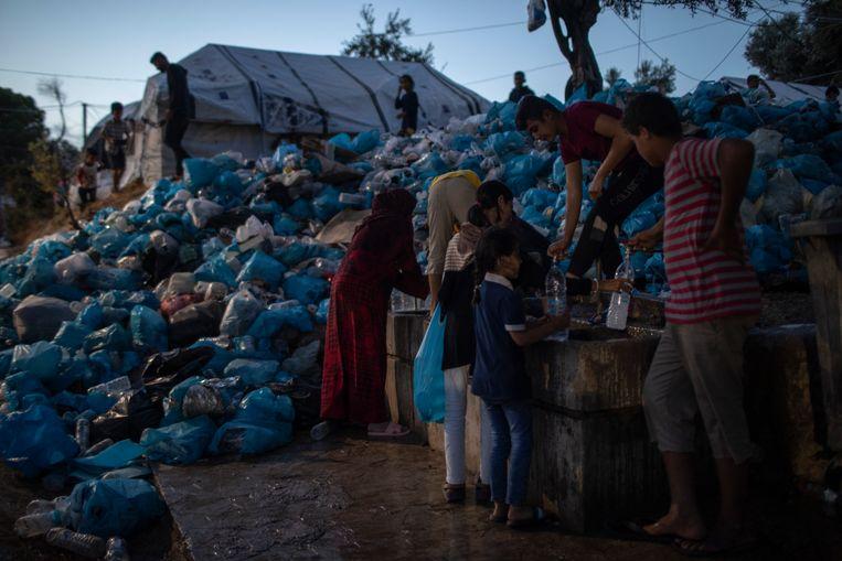 Mensen vullen flesjes met water vlak bij een berg vuilnis in he kamp Moria, op het Griekse eiland Lesbos. Beeld AP