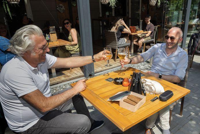 Arjen Mens (links) en Sefer Turan genieten ervan op een zonnig terras bij Paviljoen Genneper Parken in Eindhoven.