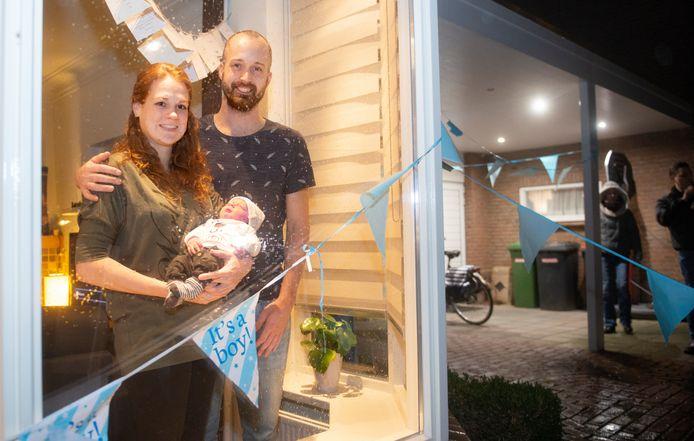 Deen van Grunsven met zijn ouders Merly Emons en Perrijn van Grunsven voor het raam van hun woning.
