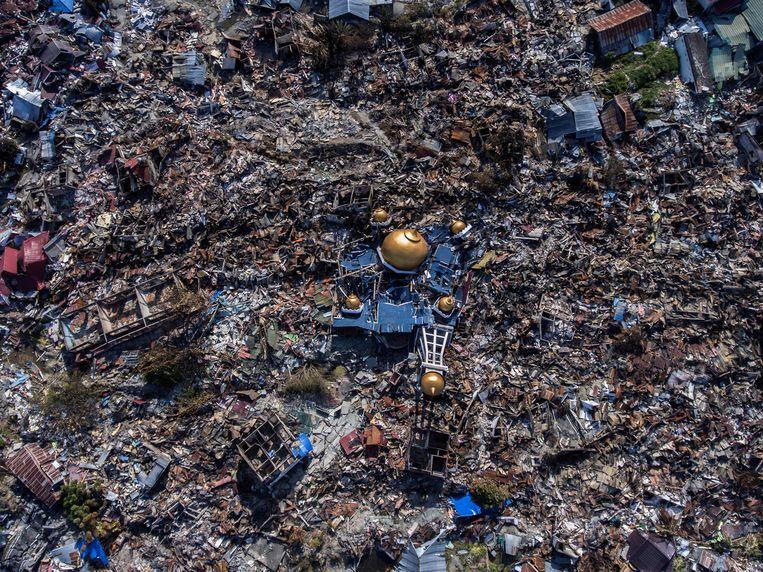 De moskeekoepels zijn nog intact, voor de rest blijft er niet veel over van Palu, de hoofdstad van de Indonesische provincie Midden-Celebes. Van de circa 300.000 inwoners hebben er vele honderden de ramp niet overleefd. Beeld ANTARA FOTO