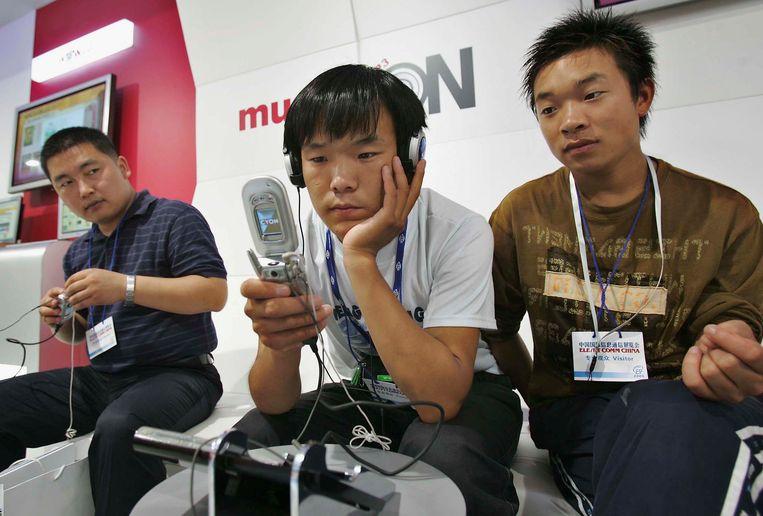 Bezoekers van een techbeurs in Shanghai proberen de nieuwste telefoon van LG in 2005. Beeld Getty Images