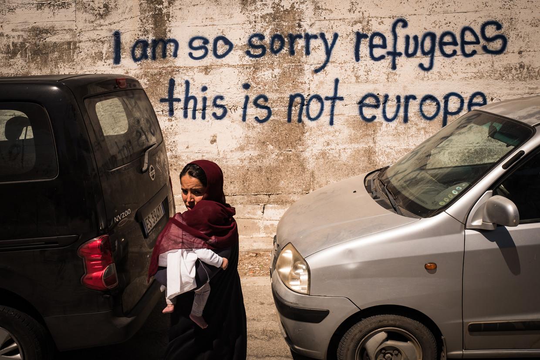 Een Afghaanse draagt haar kind op haar arm net buiten het kamp Moria op het eiland Lesbos. Beeld Nicola Zolin