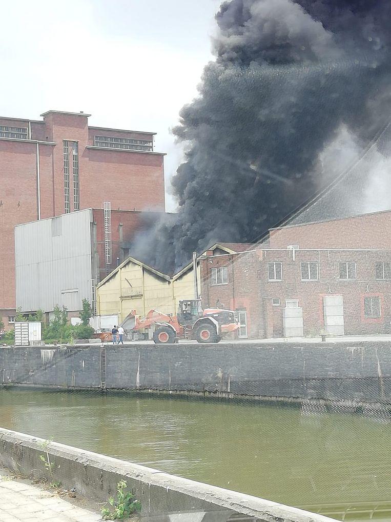 De zwarte rookwolk stijgt op uit het magazijn.