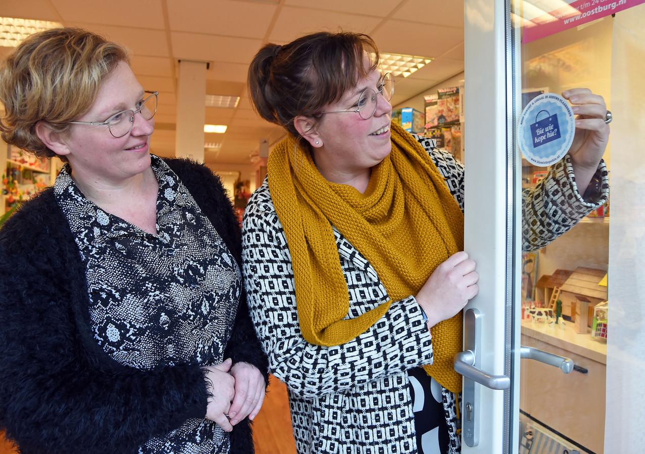 Odile de Pooter (rechts) plakt een sticker op de voordeur van winkel Sien & Kamiel. Links eigenaresse Annelies Modde.
