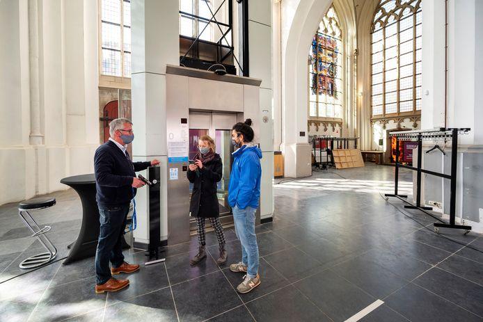 Vrijwilliger Wim Westerveld begeleidt twee bezoekers in de Arnhemse Eusebiuskerk naar boven.