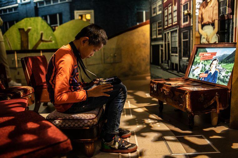Li van den Berg (11, doof) bekijkt in het Verzetsmuseum de videotour op de iPad. Beeld Nosh Neneh