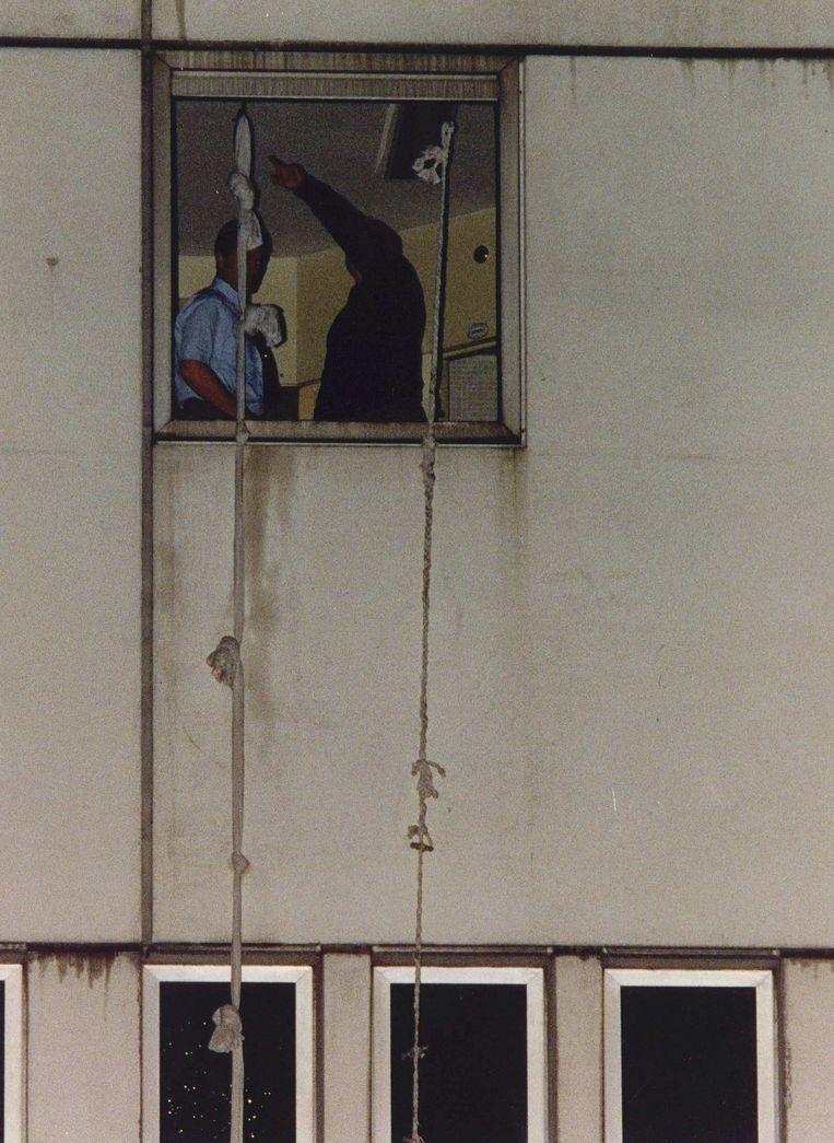 Bewakers bekijken in 1993 hoe aan elkaar geknoopte lakens aan de kozijnen van de Bijlmerbajes zijn vastgemaakt. Vanaf de eerste etage wisten vier gedetineerden daarmee te ontsnappen. Beeld Foto ANP