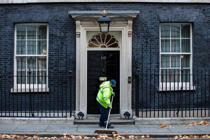 Een Londense straatveger veegt het stoepje voor Downing Street 10. Foto Jack Taylor