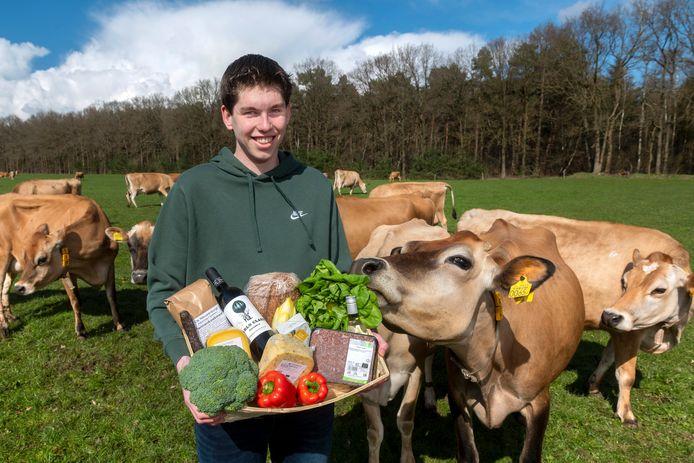Youri Nieuwenburg te midden van de koeien van zijn ouders met lokale producten die hij via zijn website verkoopt.