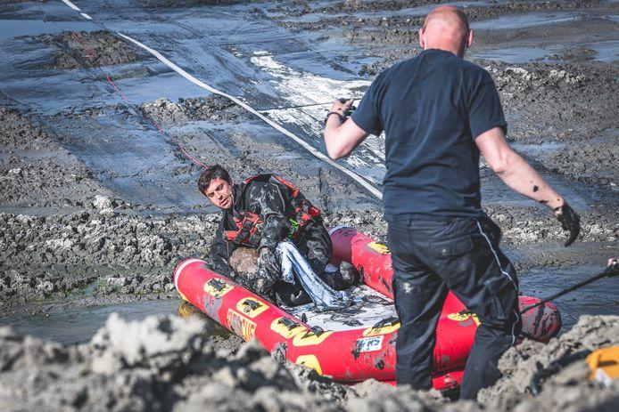 Enkele brandweermannen halen het reetje uit de modder.