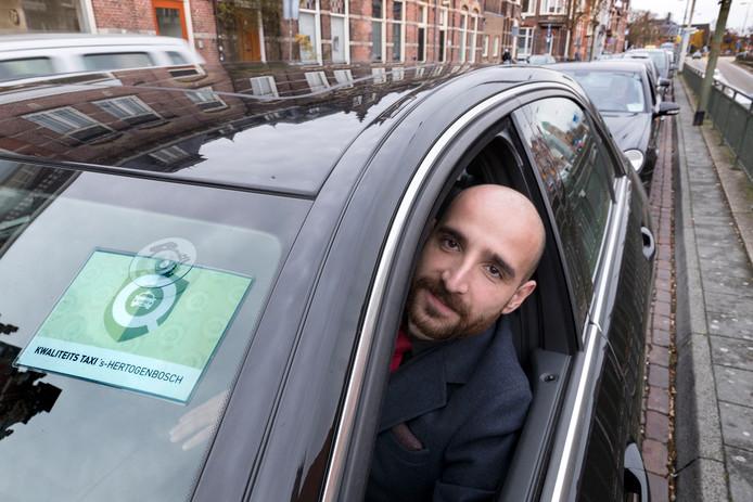 Elham Said van Taxi Maaspoort bij het Centraal Station in Den Bosch. Op de voorruit is het  kwaliteitskeurmerk geplakt.
