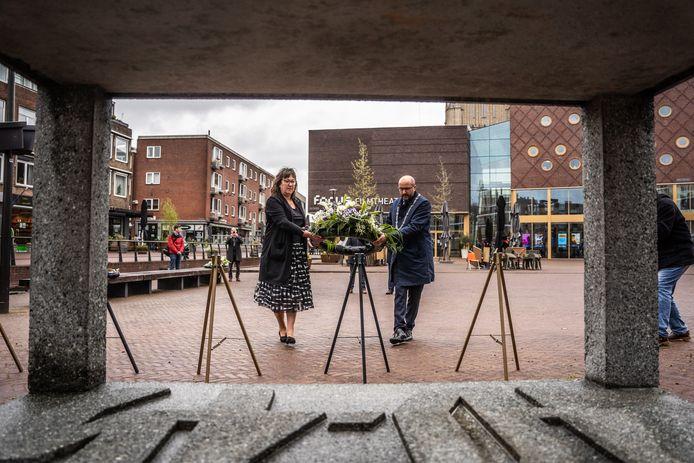 Burgemeester van Arnhem Ahmed Marcouch en vicevoorzitter van de gemeenteraad Karin Kalthoff leggen een krans bij het monument 'Mens tegen Macht' op het Audrey Hepburnplein in het stadshart.
