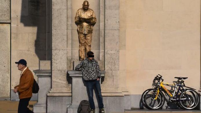 Een screenshot uit het filmpje, waarin de dief een straatartiest wil bestelen aan de Drie Gapers in Oostende.