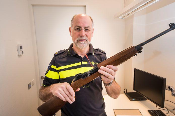 Ruud Gengler in de speciale controleruimte van het politiebureau in Enschede - zijn werkplek. Gengler is eindverantwoordelijk bij de politie in de districten IJsselland en Twente dat 100 procent van alle verplichte controles van schietsport- en jachtwapens jaarlijks wordt gehaald. Op de foto houdt hij een ERMA karabijn .22 vast.