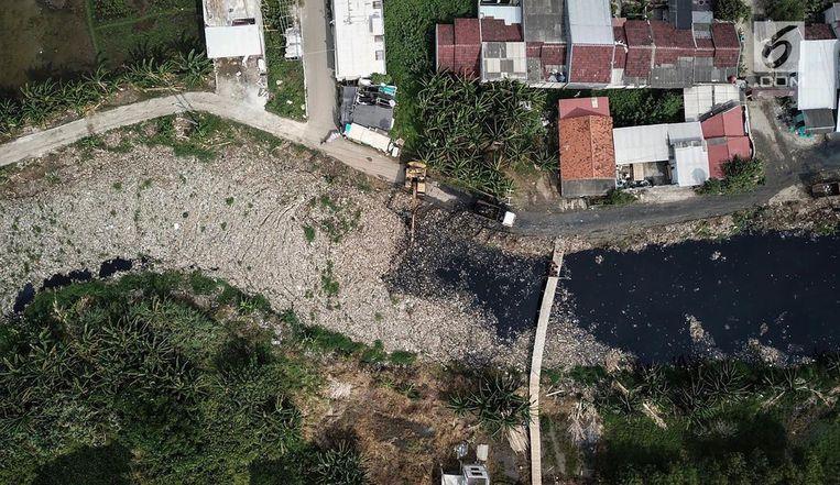 De Kali Pisang Batu is vastgelopen op de brug bij Desa Pahlawan Setia. Jutters zoeken naar iets bruikbaars op de vuilnisberg waar het afval uit de rivier wordt gestort. Beeld Fery Pradolo