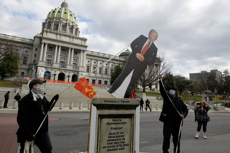 Activisten trekken een kartonnen 'standbeeld' van president Trump omver  voor het State Capitol van Pennsylvania in Harrisburg. Beeld AP