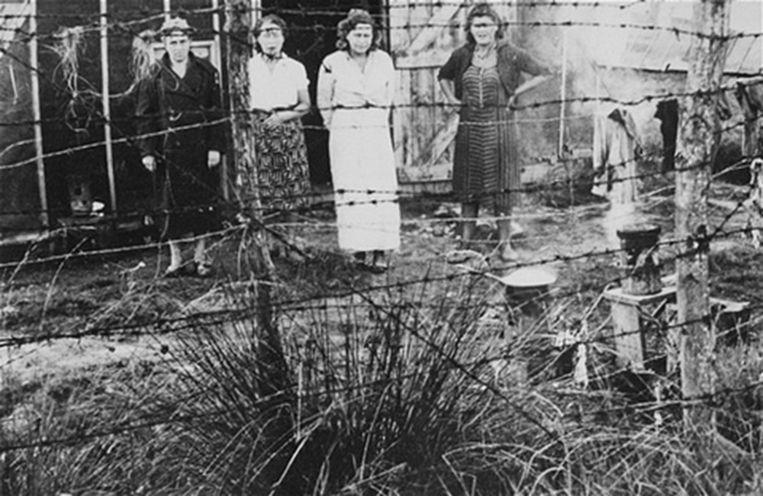 Joodse vrouwen staan bij de prikkeldraad die het kamp in Gurs, Frankrijk omringt, in de vroege jaren 40.  Beeld RV US Holocaust Memorial Museum