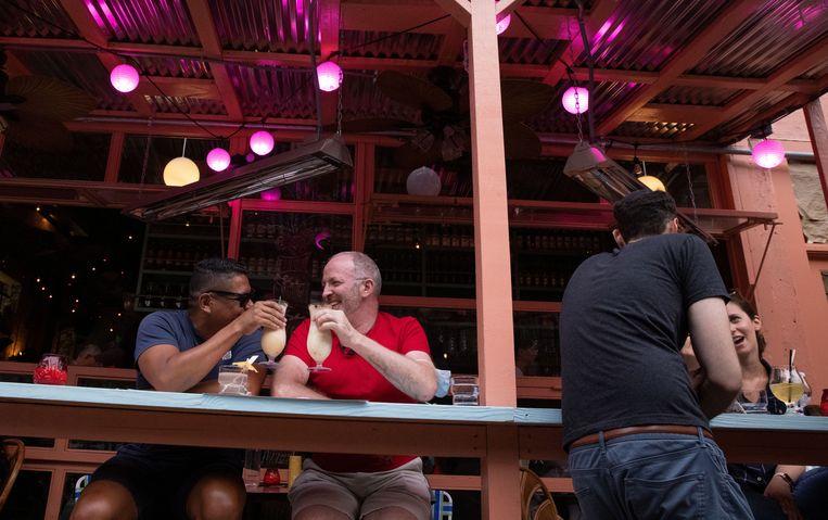 Klanten genieten van een drankje op een terras. Beeld REUTERS