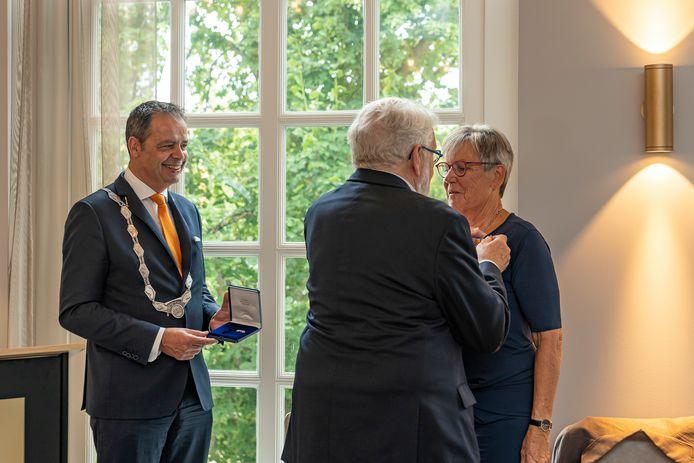 In verband met de coronabeperkingen laat burgemeester Jack van der Hoek de eer van het opspelden van de koninklijke onderscheiding bij Ria Schoof-Klaassen over aan haar echtgenoot Jaap.