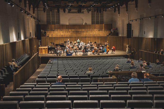 De vernieuwde concertzaal van De Bijloke ziet eruit als een pareltje, met stemmig grijze zetels en houten lambriseringen  langs de wanden. Achter de musici zijn nieuwe koorbanken aangebracht.