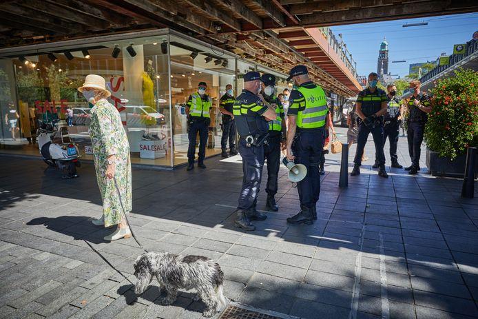 Waar agenten de demonstranten tegen houden, loopt een dame gemoedelijk langs met haar hond én een mondkapje op. Alsof het dagelijkse kost is.
